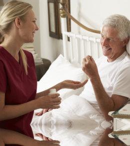 staff giving medicine to elder man